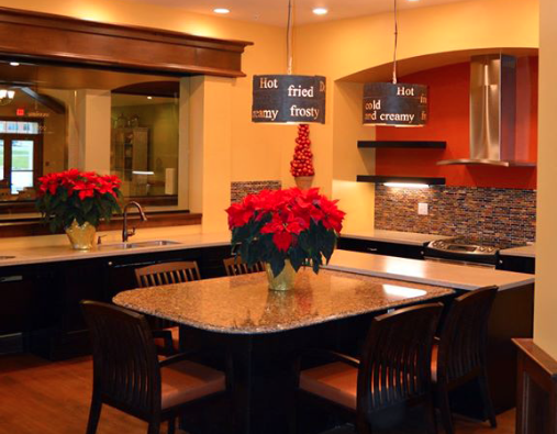 A small kitchen and dining area at Stillwater Senior Living in Edwardsville, IL. This personal, home-style dining area provides an accessible sink and stove and represents a major trend in senior living interior design.